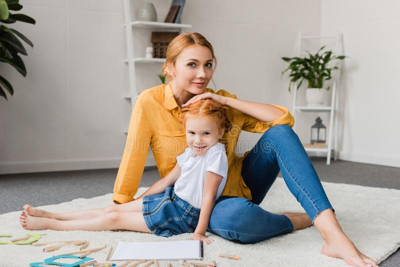 Mãe e filha que sentam-se no assoalho imagem de stock