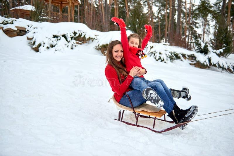 Mãe e filha que sledding na neve na floresta fotos de stock royalty free