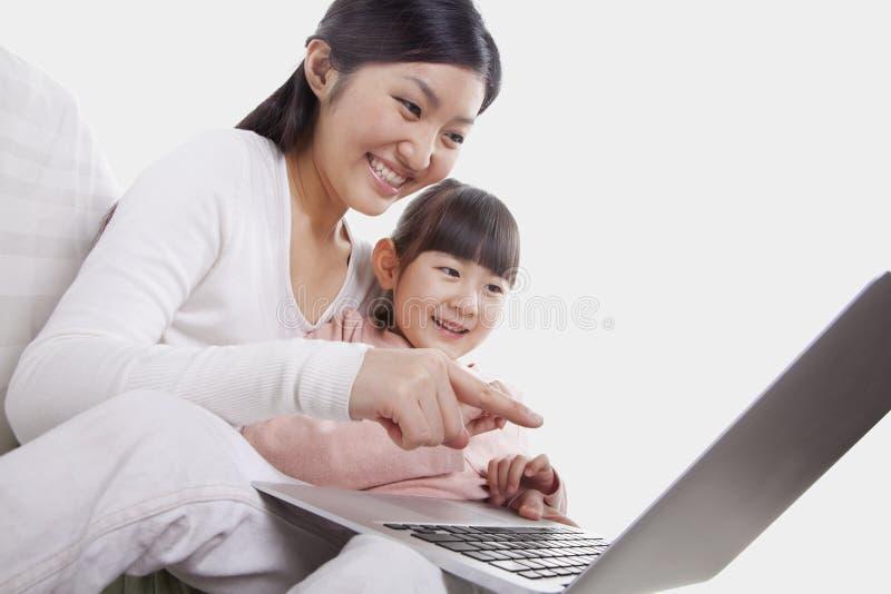 Mãe e filha que sorriem e que sentam-se perto junto no sofá, usando-se e apontando no portátil, inclinação fotos de stock royalty free