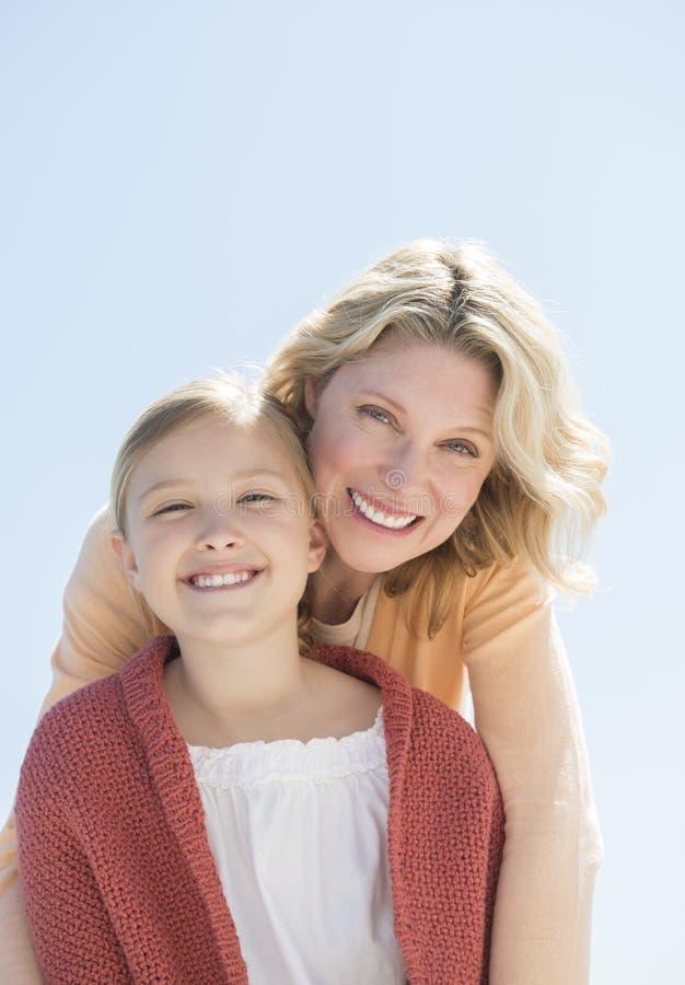 Mãe e filha que sorriem junto contra o céu azul claro imagens de stock