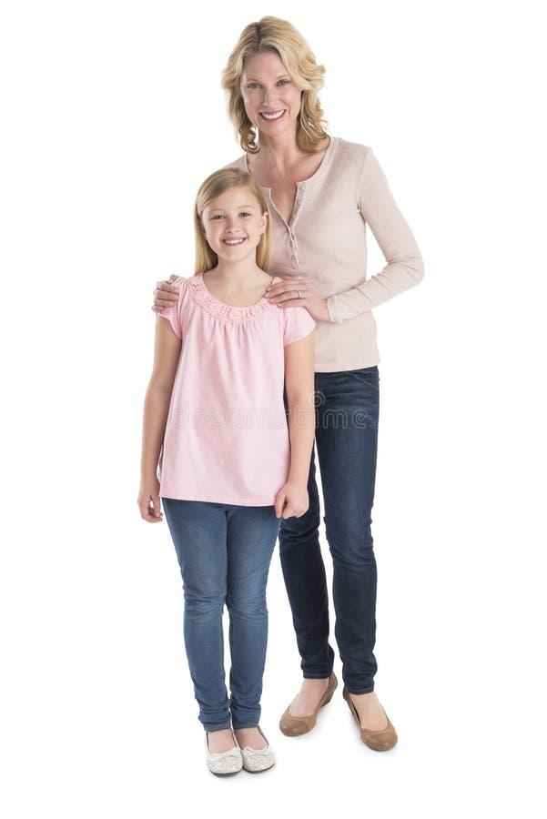 Mãe e filha que sorriem junto sobre o fundo branco fotografia de stock
