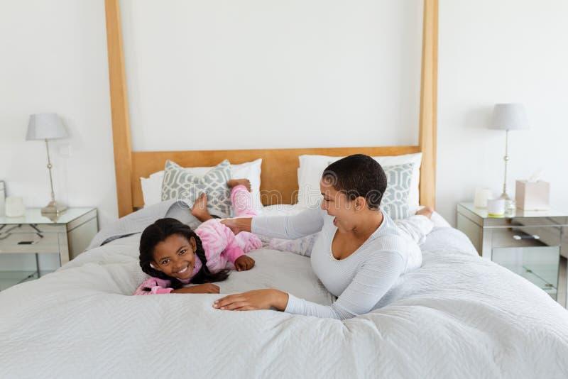 Mãe e filha que têm o divertimento na cama no quarto fotos de stock royalty free