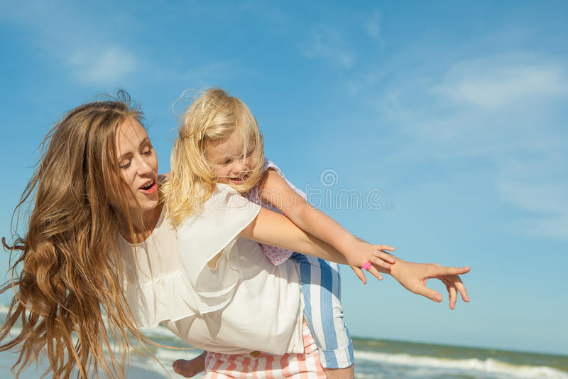 Mãe e filha que têm o divertimento que joga na praia foto de stock