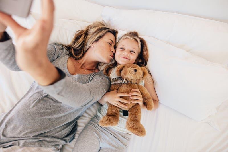Mãe e filha que tomam o selfie na cama fotografia de stock
