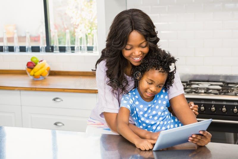 Mãe e filha que usa o PC da tabuleta foto de stock