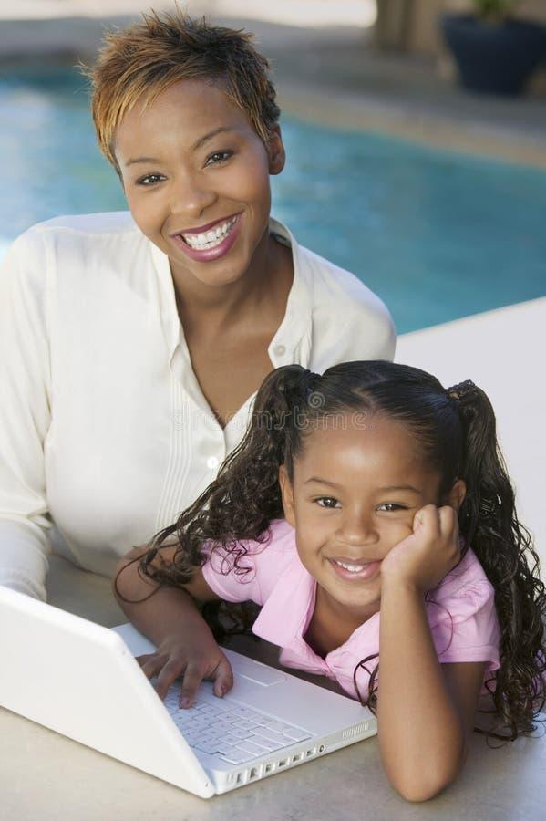 Mãe e filha que usa o portátil na opinião de ângulo alto do retrato do pátio foto de stock