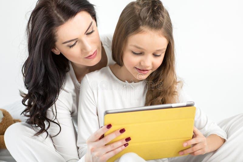 Mãe e filha que usa a tabuleta digital junto imagens de stock royalty free