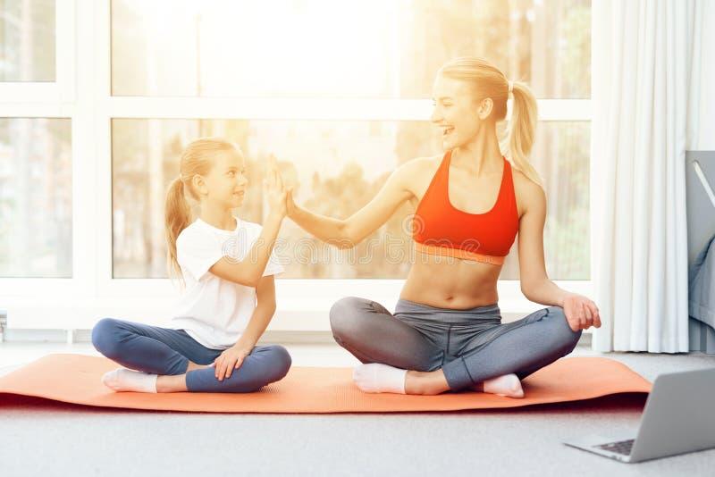 A mãe e a filha são contratadas na ioga no sportswear Estão em uma sala brilhante com janelas panorâmicos imagens de stock