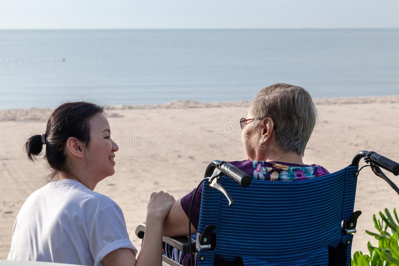 A mãe e a filha sentam-se junto na frente da praia que olha se imagem de stock