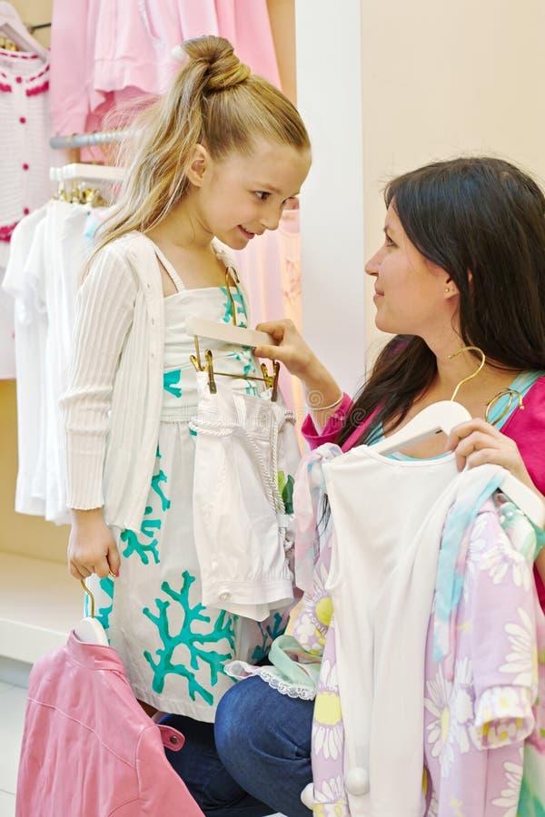 A mãe e a filha tentam sobre a roupa fotos de stock