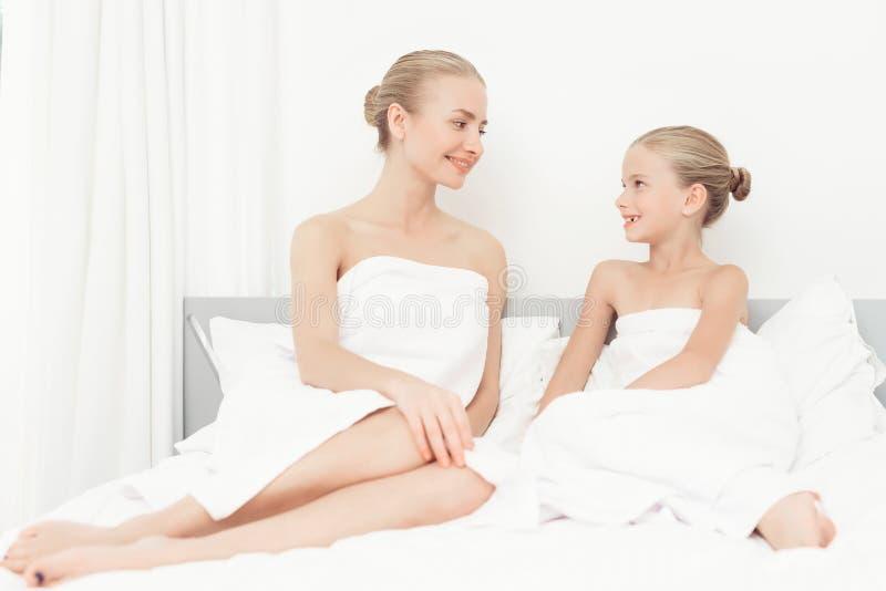 A mãe e a filha tiveram um dia dos termas Têm o divertimento nas toalhas de banho brancas imagens de stock royalty free