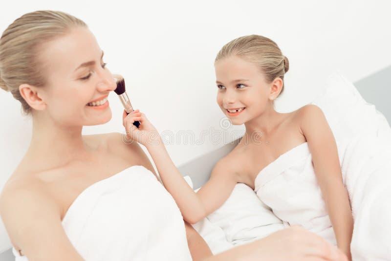 A mãe e a filha tiveram um dia dos termas Têm o divertimento nas toalhas de banho brancas fotografia de stock royalty free