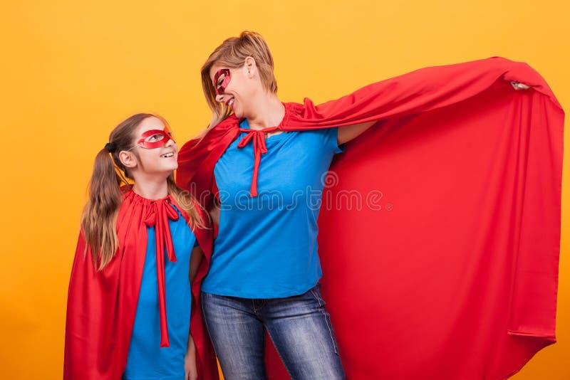 Mãe e filha vestidas como os superheros que ligam-se sobre o fundo amarelo fotografia de stock royalty free