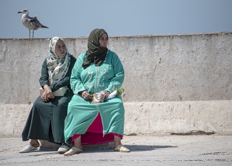 A mãe e a filha, vestidas no abaya e no hijab, tomam um assento ao longo da parte dianteira do porto imagens de stock