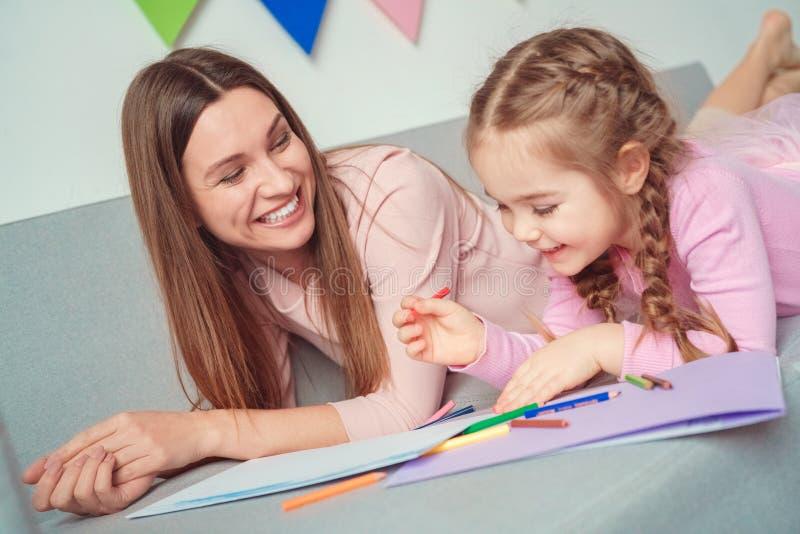 A mãe e a filha weekend junto em casa no riso do desenho do sofá imagem de stock