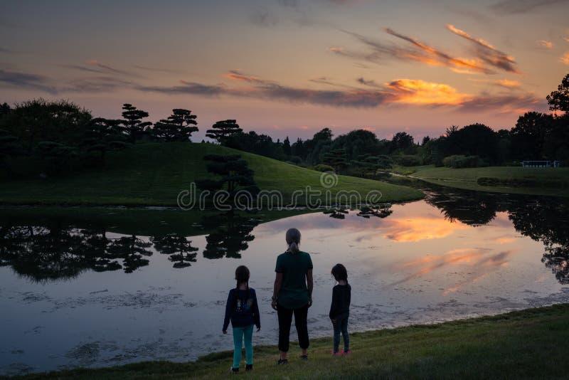 Mãe e filhas no lago no por do sol imagens de stock royalty free