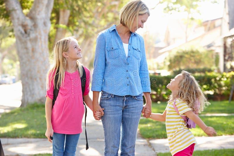Mãe e filhas que andam à escola na rua suburbana fotos de stock