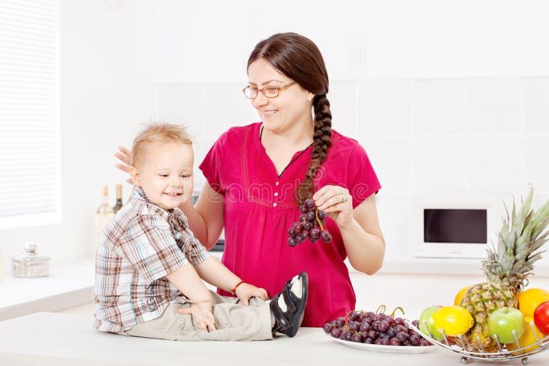 Mãe e filho com frutos na cozinha imagem de stock