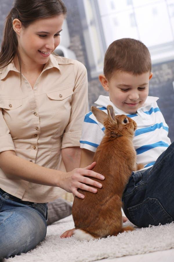 Mãe e filho com o coelho bonito do animal de estimação imagem de stock