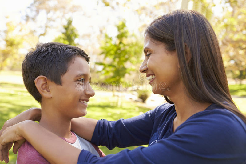 Mãe e filho da raça misturada em um parque, olhando se imagem de stock