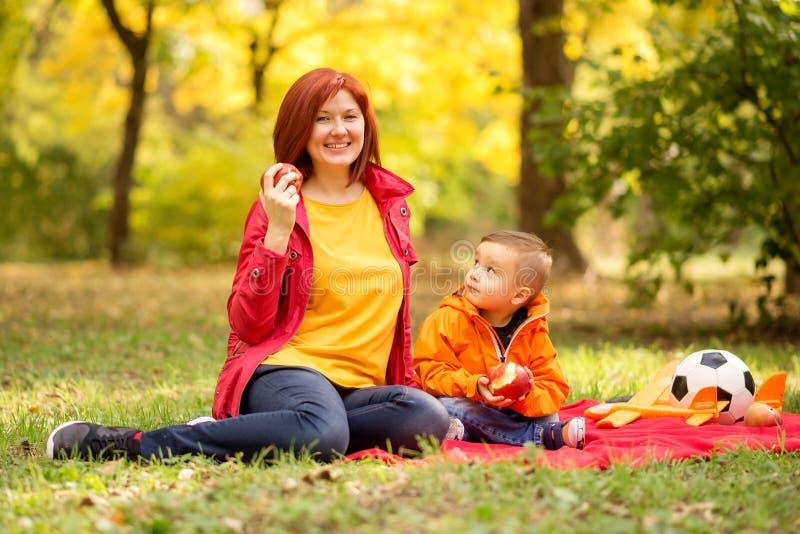 Mãe e filho de criança no piquenique de outono no parque ou floresta A educação saudável e o lazer familiar ativo ao ar livre são fotos de stock royalty free
