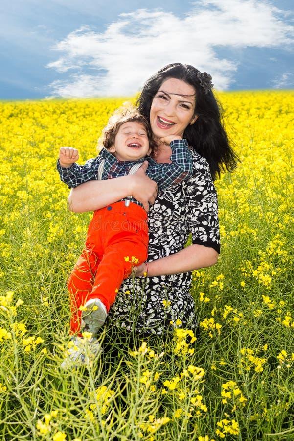 Mãe e filho de riso no campo do canola imagem de stock royalty free