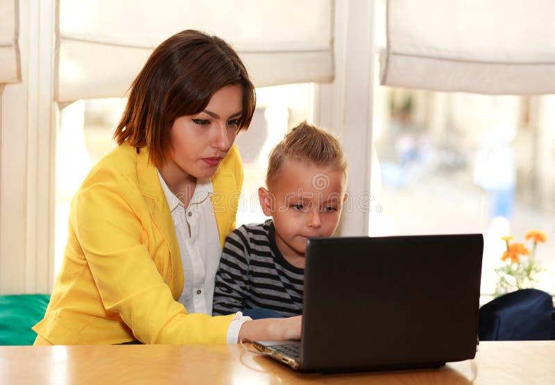 Mãe e filho em casa que fazem a lição que olha o portátil imagem de stock