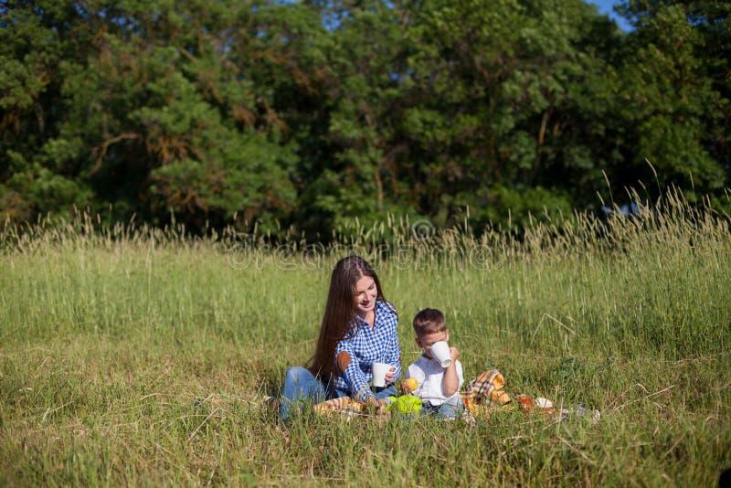 Mãe e filho em um feriado comer do ar livre do piquenique fotos de stock