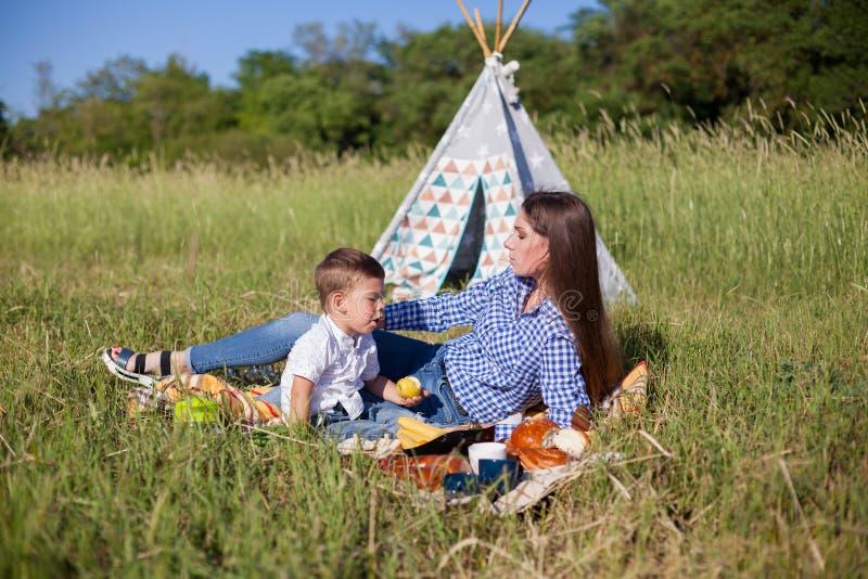 Mãe e filho em um feriado comer do ar livre do piquenique imagem de stock