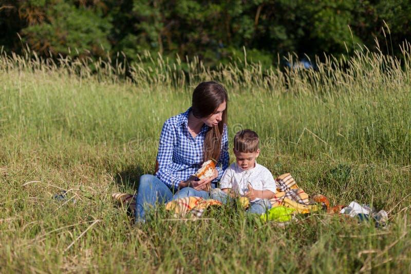 Mãe e filho em um olhar do feriado comer do ar livre do piquenique imagens de stock royalty free