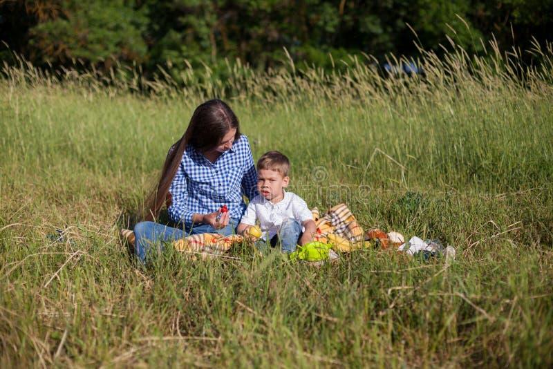 Mãe e filho em um olhar do feriado comer do ar livre do piquenique fotografia de stock royalty free
