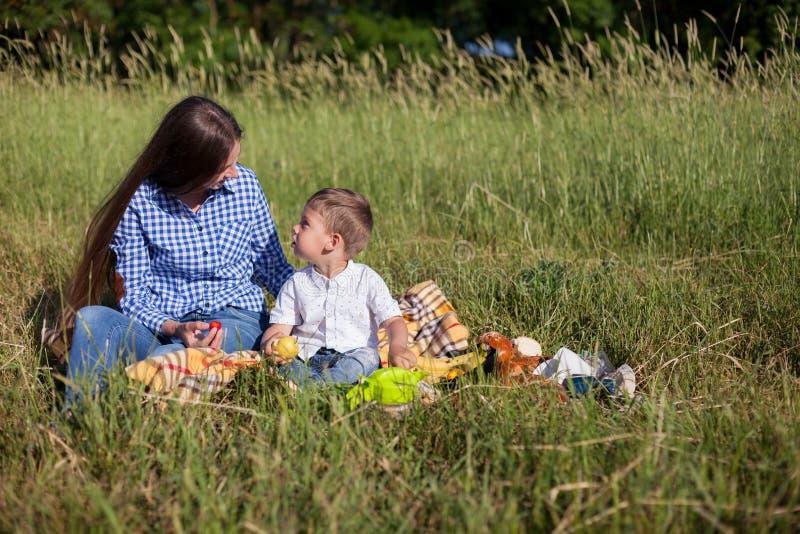 Mãe e filho em um olhar do feriado comer do ar livre do piquenique fotos de stock