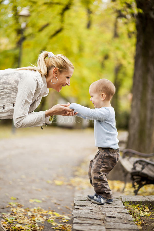 Mãe e filho na floresta do outono imagem de stock
