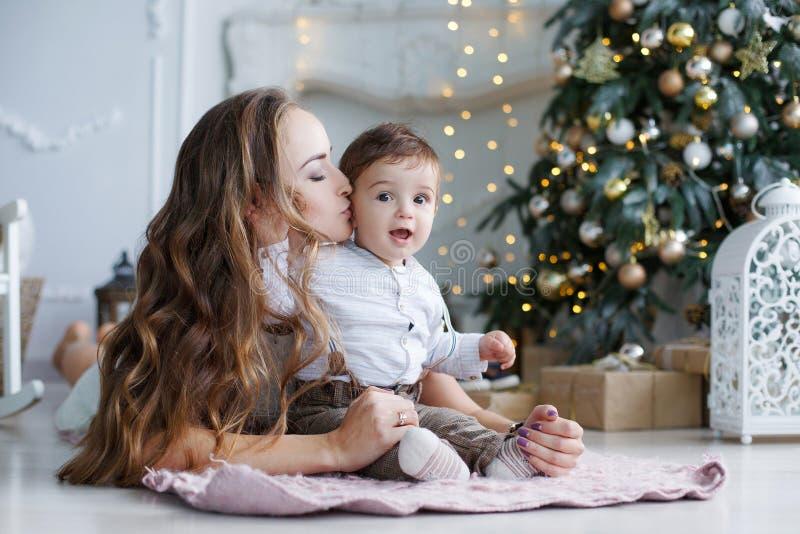 Mãe e filho novo em casa perto da árvore de Natal fotografia de stock