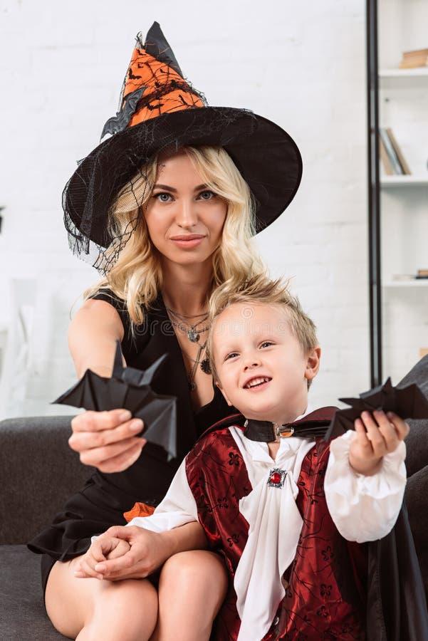 mãe e filho pequeno nos trajes do Dia das Bruxas que mostram bastões de papel pretos no sofá imagem de stock royalty free