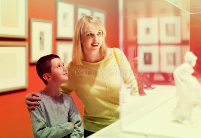 Mãe e filho que apreciam exposições no museu fotografia de stock