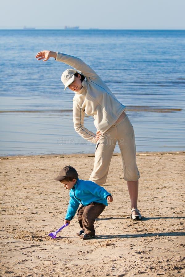 Mãe e filho que apreciam o tempo na praia imagens de stock