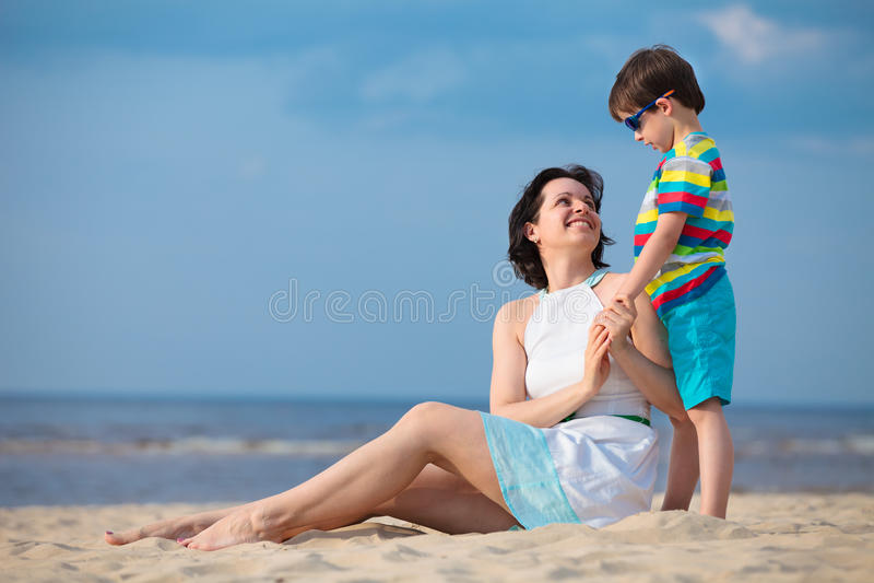 Mãe e filho que apreciam o tempo na praia tropical foto de stock