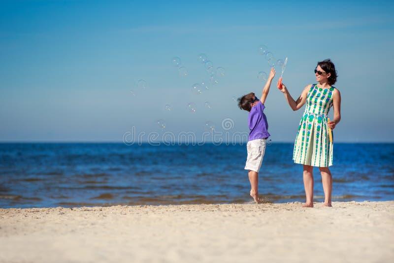 Mãe e filho que apreciam o tempo na praia tropical imagem de stock