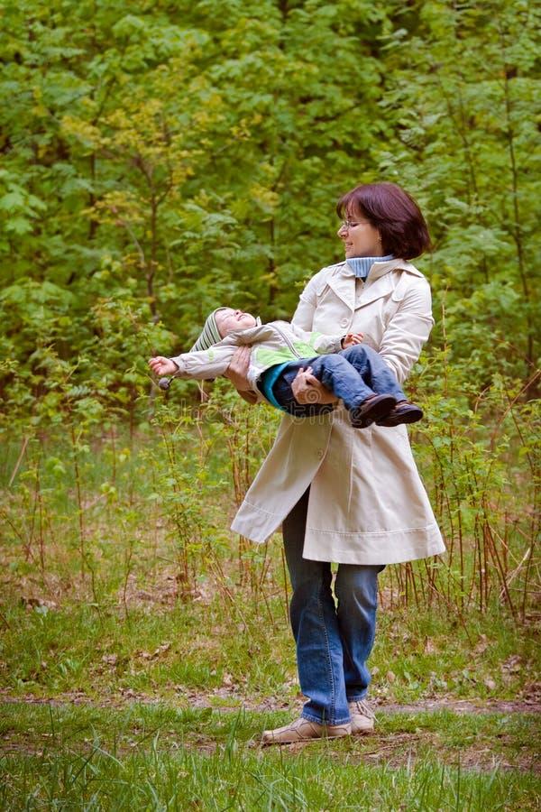 Mãe e filho que apreciam o tempo no parque da mola fotografia de stock royalty free
