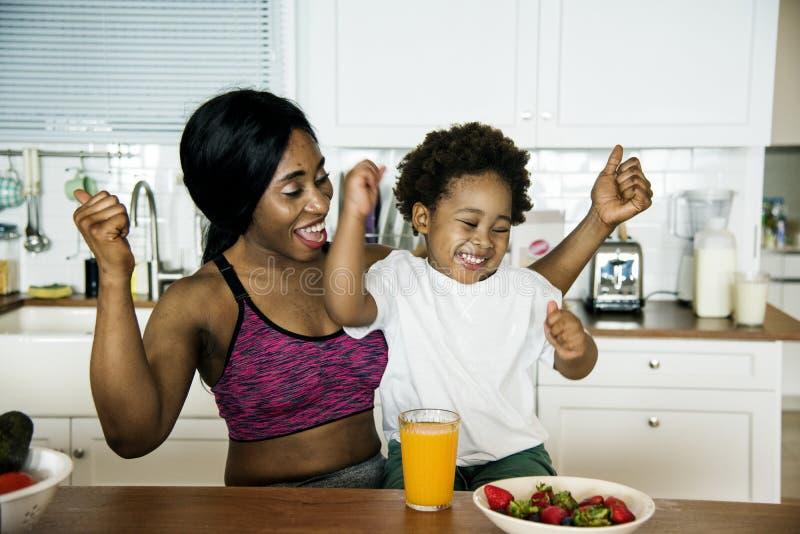 Mãe e filho que comem o alimento saudável na cozinha imagens de stock