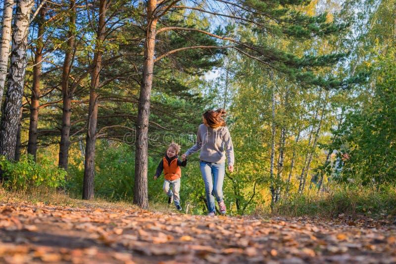 Mãe e filho que correm no trajeto na floresta do outono fotografia de stock royalty free