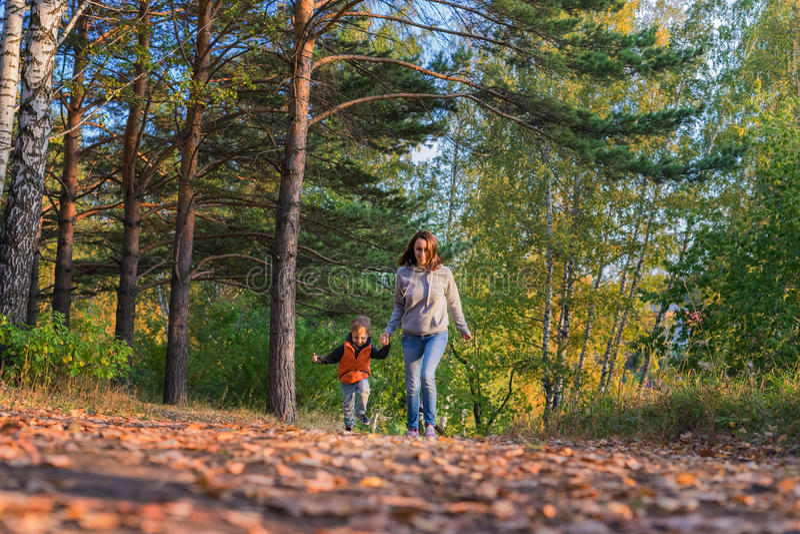 Mãe e filho que correm no trajeto na floresta do outono fotografia de stock