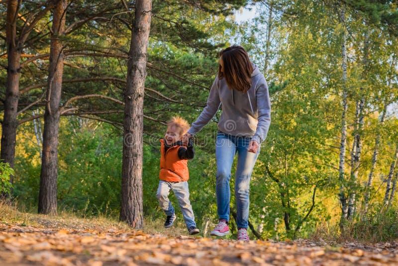 Mãe e filho que correm no trajeto na floresta do outono imagem de stock royalty free