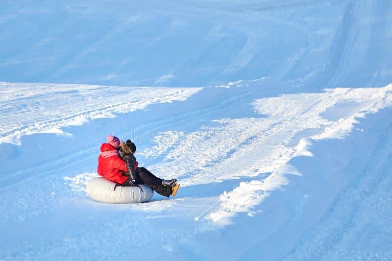 Mãe e filho que deslizam na tubulação da neve abaixo do monte fotos de stock