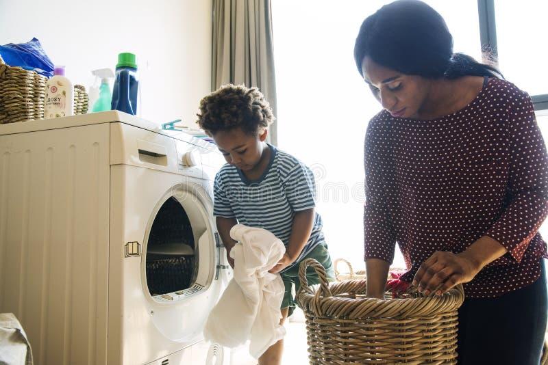 Mãe e filho que fazem trabalhos domésticos junto fotografia de stock