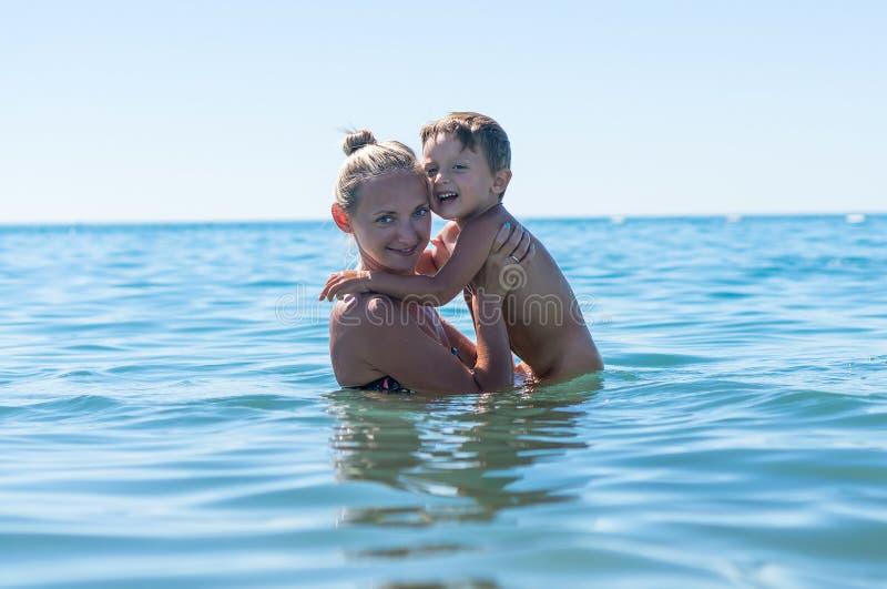 Mãe e filho que jogam na praia no tempo do dia Retrato do menino feliz da criança na praia do oceano Maki bonito engraçado da cri fotografia de stock royalty free