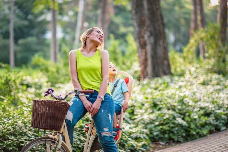 Mãe e filho que montam uma bicicleta junto na família feliz do parque imagem de stock royalty free
