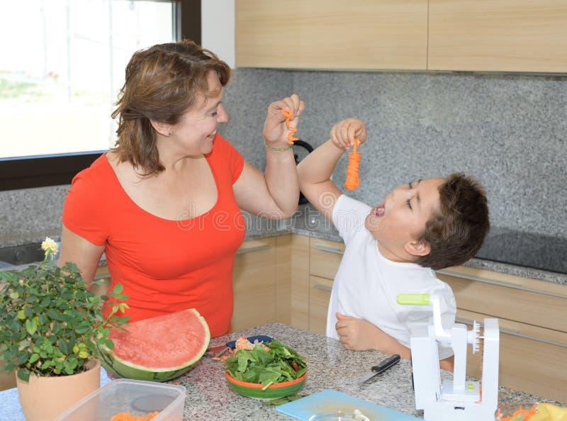 Mãe e filho que preparam o almoço e os sorrisos Gracejam com uma cenoura cinzelada fotografia de stock