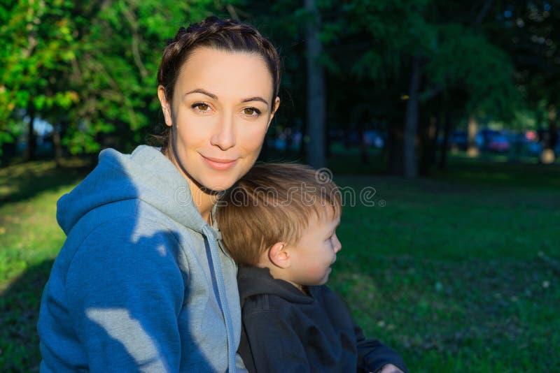 Mãe e filho que sentam-se na grama imagem de stock royalty free